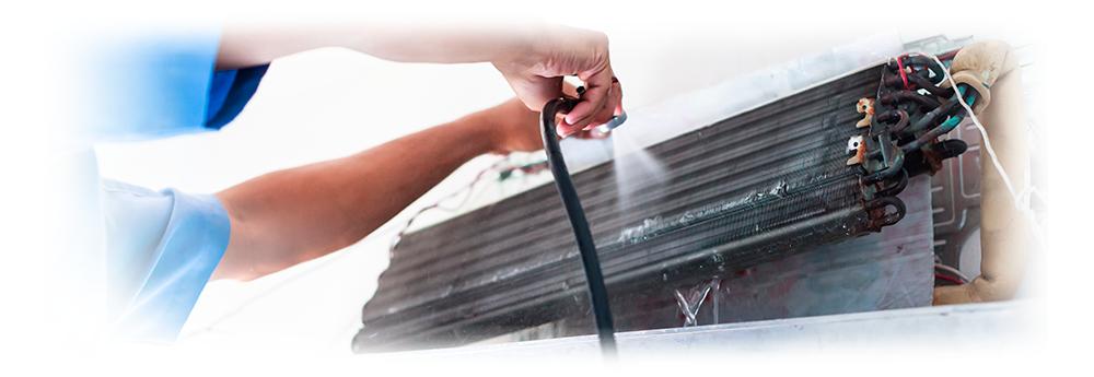 Duas mãos realizando a limpeza de um ar condicionado aberto