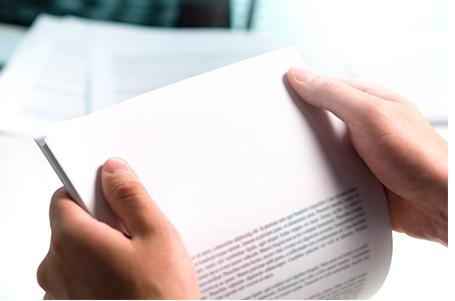 Duas mãos segurando um contrato de PMCO, dando a entender que a pessoa está lendo.